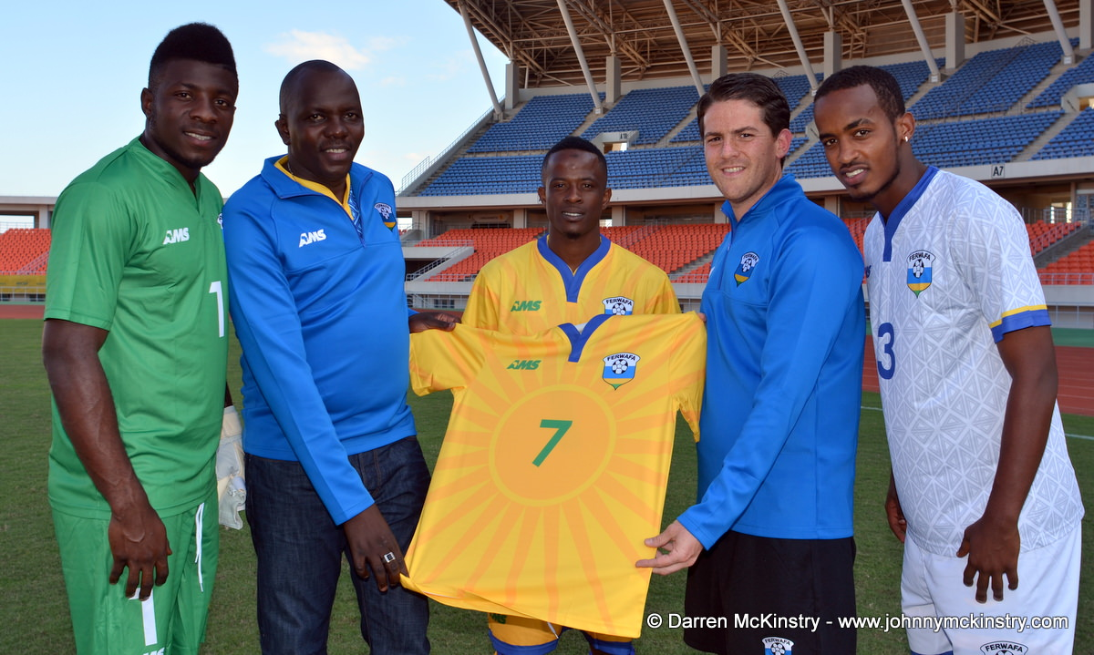 L-R: Olivier Kwizera (Goalkeeper);  Jean-Olivier Mulindahabi (General Secretary, FERWAFA); Haruna Niyonzima (Captain); Coach McKinstry; Yannick Mukunzi  with the new Rwanda Amavubi Home Shirt by AMS  [Players are modelling new goalkeeping; home and away kits by AMS.  Pictured at Training camp ahead of Rwanda Amavubi v Mozambique, 13 June 2015  (Pic © Darren McKinstry / www.johnnymckinstry.com)]